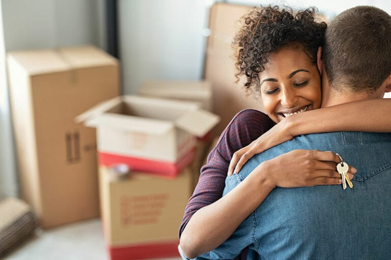 Smiling couple with house keys hugging amidst empty cardboard boxes