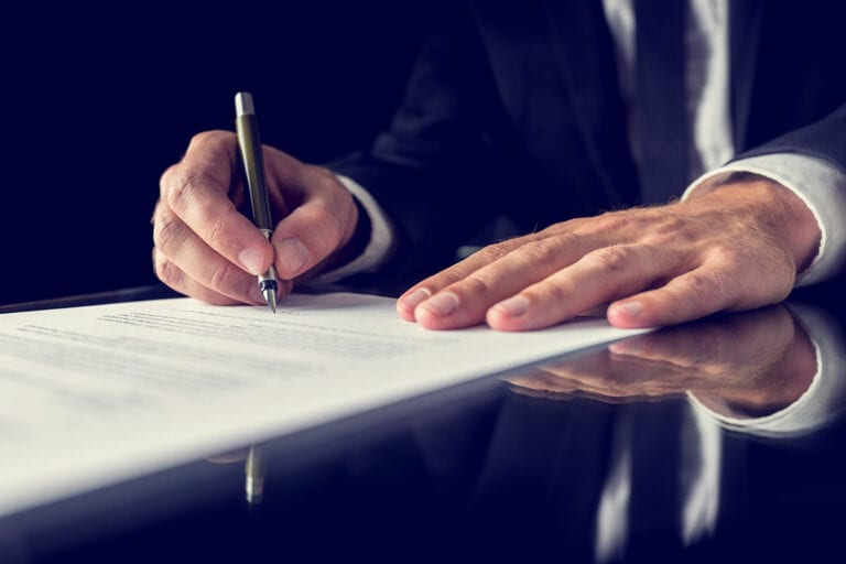 man's hands holding fountain pen signing legal document