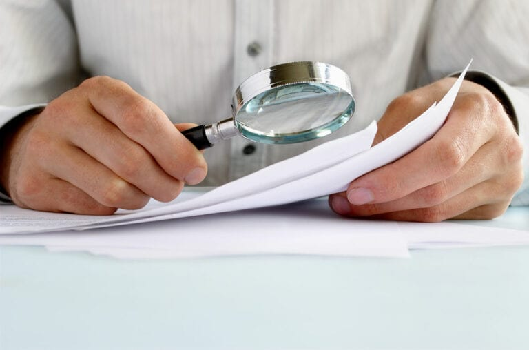 man's hands holding magnifying glass examining documents